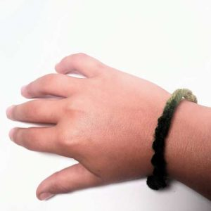 Green and tan yarn bracelet on child's wrist